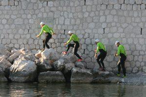 Les quatre pionniers de l'ultraswimrun courent dans les rochers sur la plage de Passable